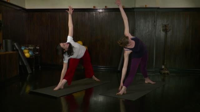 stockvideo's en b-roll-footage met ws two women doing yoga exercise / brooklyn, new york, usa - benen gespreid