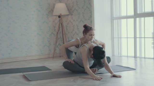 vídeos de stock, filmes e b-roll de duas mulheres fazendo ioga meditação e alongamentos - instrutor de fitness