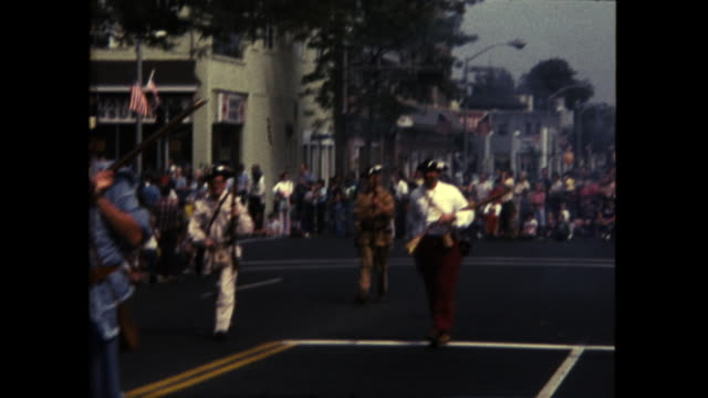 two women dressed in colonial dress holding american flags followed by men shooting rifles into the air crowd watching in the background - 道路名の標識点の映像素材/bロール