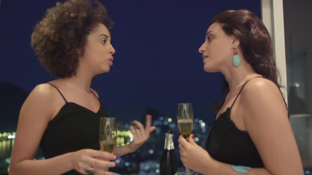 ms two women drink champagne together / rio de janeiro, brazil - パルド人点の映像素材/bロール