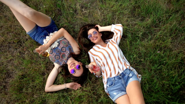 two women drinking and playing in meadow - sunglasses stock videos & royalty-free footage