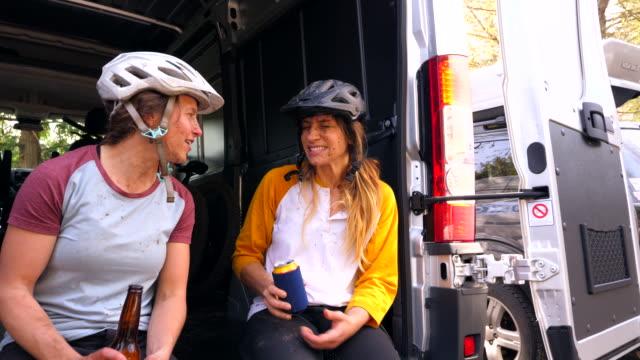 ms two women drinking beer together after muddy mountain bike ride - vuxen bildbanksvideor och videomaterial från bakom kulisserna