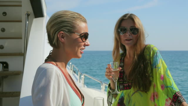 stockvideo's en b-roll-footage met ms two women drinking champagne and chatting on luxury yacht / portals nous, mallorca, spain - dranken
