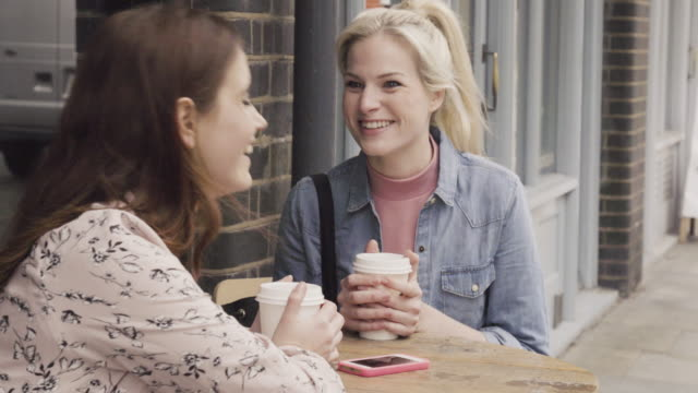 Two women drinking coffee and chatting , sitting at cafe table, outdoors.
