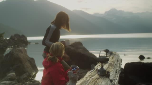 ms td two women drinking tea sitting on log at campsite by lake garibaldi, garibaldi provincial park, squamish, british columbia, canada - garibaldi park stock videos & royalty-free footage