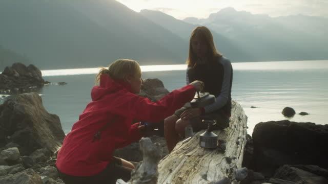 ms two women drinking tea sitting on log at campsite by lake garibaldi, garibaldi provincial park, squamish, british columbia, canada - garibaldi park stock videos & royalty-free footage