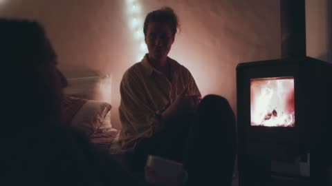 two women drinking tea, talking in front of fireplace - erwachsene person stock-videos und b-roll-filmmaterial
