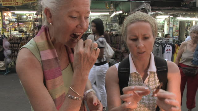 CU Two women eating grasshoppers in busy city street, Bangkok, Thailand