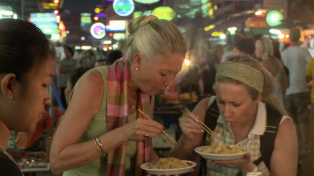 CU Two women eating Pad Thai food in city street at night, Bangkok, Thailand