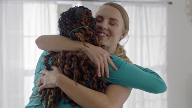 vídeos de stock, filmes e b-roll de slo mo. two women embrace after yoga workout in home studio. - encorajamento