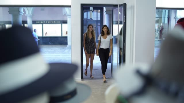 two women entering a clothing store - cappello video stock e b–roll
