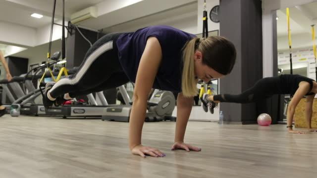 two women exercising with suspension straps at gym - allenamento a corpo libero video stock e b–roll