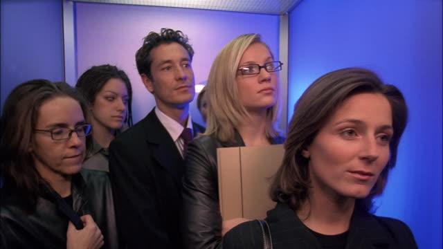 vídeos de stock e filmes b-roll de two women exit a crowded elevator. - elevador
