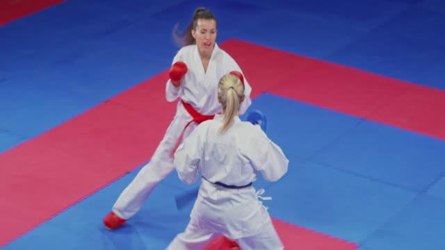 vídeos de stock, filmes e b-roll de duas mulheres que lutam em uma competição fêmea do karaté - karate