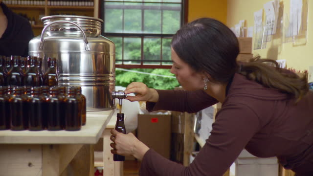 ms pan two women filling up and corking bottles with liquid from large container / burlington, vermont, usa - burlington vermont stock videos & royalty-free footage