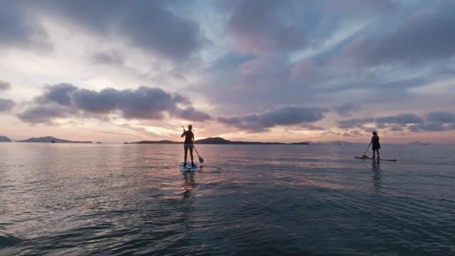stockvideo's en b-roll-footage met twee vrienden paddleboarding van vrouwen in overzees bij zonsopgang - peddel