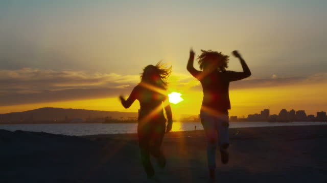 Two women friends running towards the camera at sunset