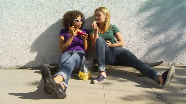Two women friends sitting on skateboards