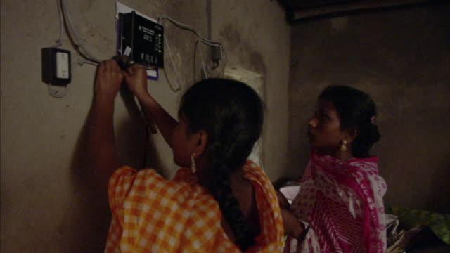 ms, two women hammering solar panel cord  to wall, mawna, bangladesh - bangladesh stock videos & royalty-free footage