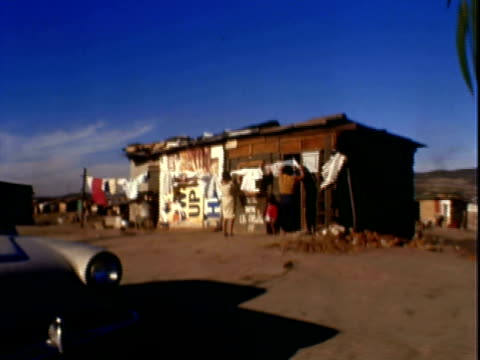two women hanging clothes on clothesline to dry outside wood shack one woman holding baby / boy using pot to collect rainwater / boys playing with... - dry clothes stock videos and b-roll footage
