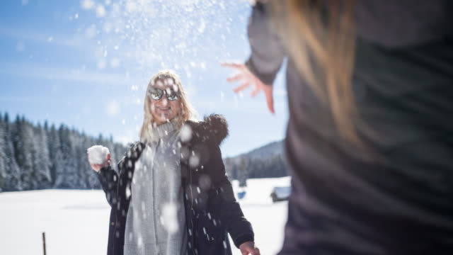 Two women having a snowball fight
