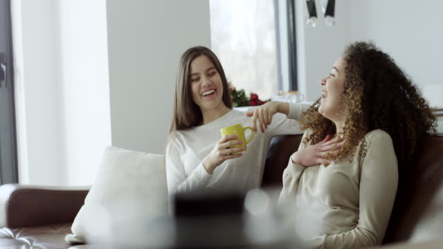 two women having coffee together on sofa - cosy stock videos & royalty-free footage