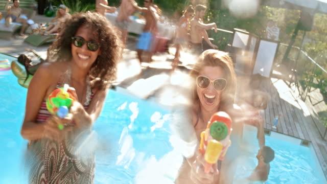 水銃、カメラに水のしぶきとプール パーティーで楽しい 2 人の女性 - 水鉄砲点の映像素材/bロール