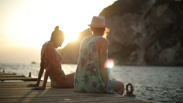 vídeos de stock e filmes b-roll de two women having fun on a pier at sunset - pier