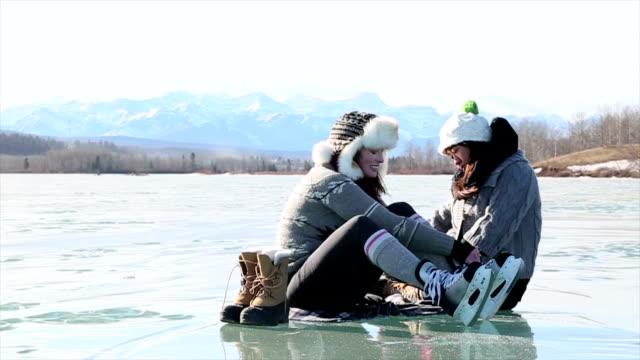 Two women having fun on frozen lake