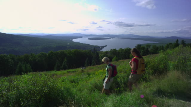 ws tu two women hiking at the height of land overlooking mooselookmeguntic lake, outside of rangeley, maine, usa - alm stock-videos und b-roll-filmmaterial