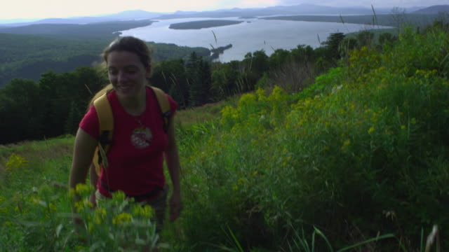ws two women hiking at the height of land overlooking mooselookmeguntic lake, outside of rangeley, maine, usa - tre quarti video stock e b–roll