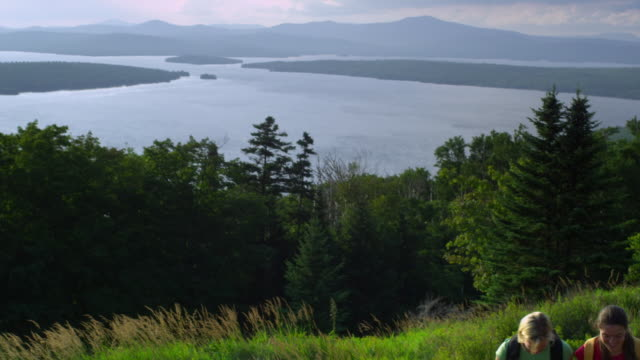 ms td two women hiking at the height of land overlooking mooselookmeguntic lake, outside of rangeley, maine, usa - tre quarti video stock e b–roll