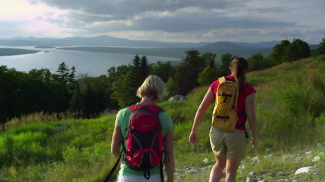 ws two women hiking at the height of land overlooking mooselookmeguntic lake, outside of rangeley, maine, usa - alm stock-videos und b-roll-filmmaterial