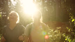 Two women hiking in the mountains with backpacks. Girls on a hike breathing fresh air oxygen. Back to nature