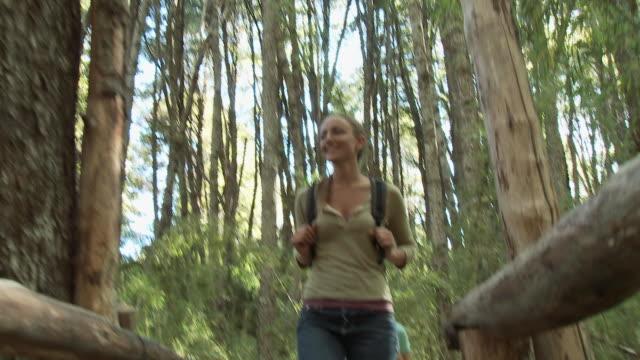 two women hiking through forest - kamerafahrt auf schienen stock-videos und b-roll-filmmaterial