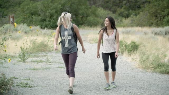 Two women hiking toward the camera.