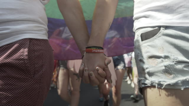 two women hold hands at pride in london parade 2018 - atmosphere on july 07, 2018 in london, england. - homosexual stock videos & royalty-free footage