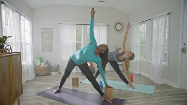 SLO MO. Two women hold Triangle pose while practicing yoga in sunny home studio.
