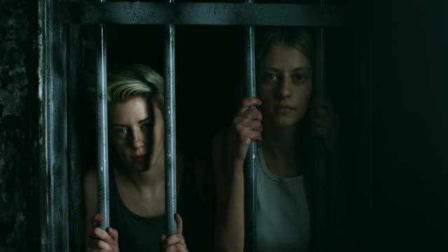 two women holding bars and looking through at prison cell - claustrophobia stock videos & royalty-free footage