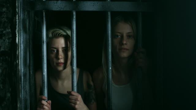 Zwei Frauen halten Bars und Gefängniszelle durch betrachten