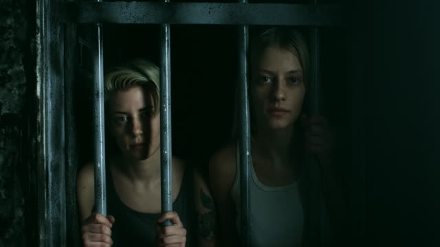 two women holding bars and looking through at prison cell - claustrophobia stock videos and b-roll footage