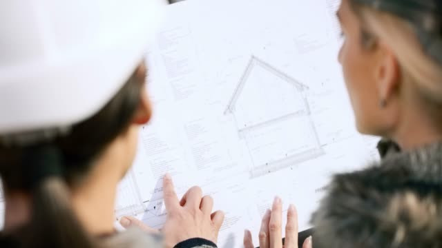 two women holding up the plans for a house and talking about it - architect stock videos & royalty-free footage