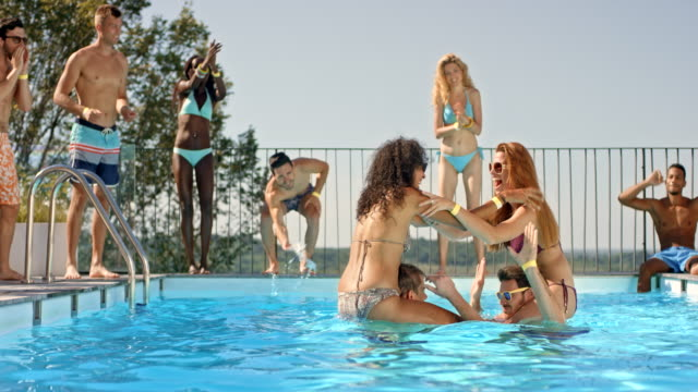 SLO MO DS Two women in a chicken fight in the pool and their friends standing by the pool and cheering for them