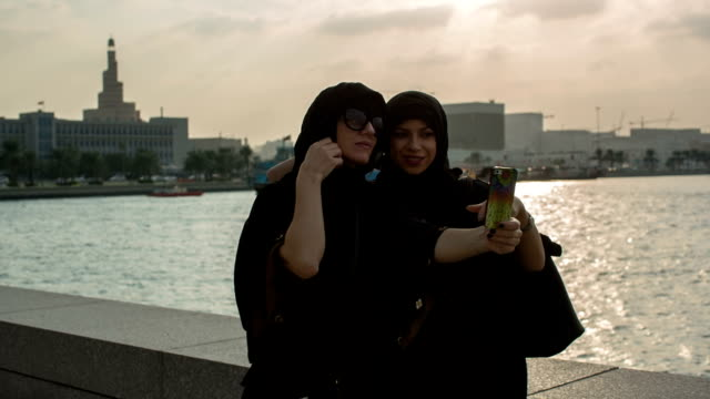 two women in abayas make selfies in front of the museum of islamic art in doha, qatar - doha bildbanksvideor och videomaterial från bakom kulisserna