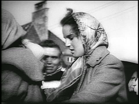 two women in babushkas outdoors / refugees after hungarian revolution / news. - dominering bildbanksvideor och videomaterial från bakom kulisserna