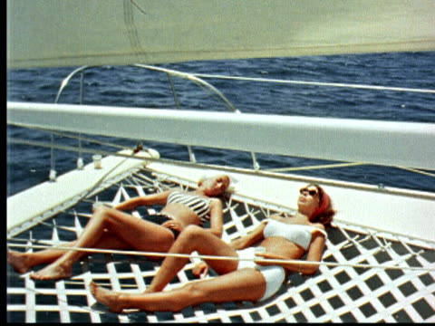 1966 montage two women in bathing suits sunbathing on webbing of catamaran sailboat / bermuda - bermuda stock videos & royalty-free footage