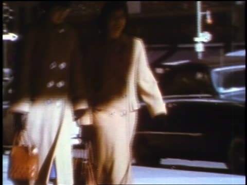 1957 two women in beige coats walking on city sidewalk / feature - 1957 stock-videos und b-roll-filmmaterial