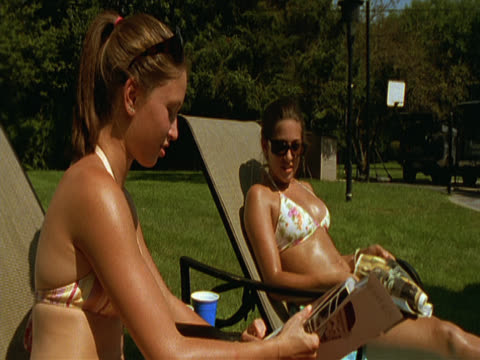 two women in bikinis are reclining on sun-loungers in a leafy garden. the woman in the foreground has sunglasses pushed back onto the top of her head. both women are talking and reading magazines. long island, new york, usa - magazine publication stock videos & royalty-free footage