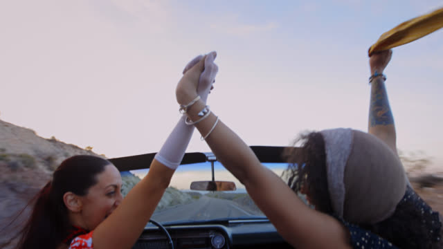 MS. Two women in classic convertible hold hands, laugh and cheer on desert road trip.