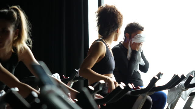 ms two women in discussion while riding stationary bikes during fitness class - handtuch stock-videos und b-roll-filmmaterial